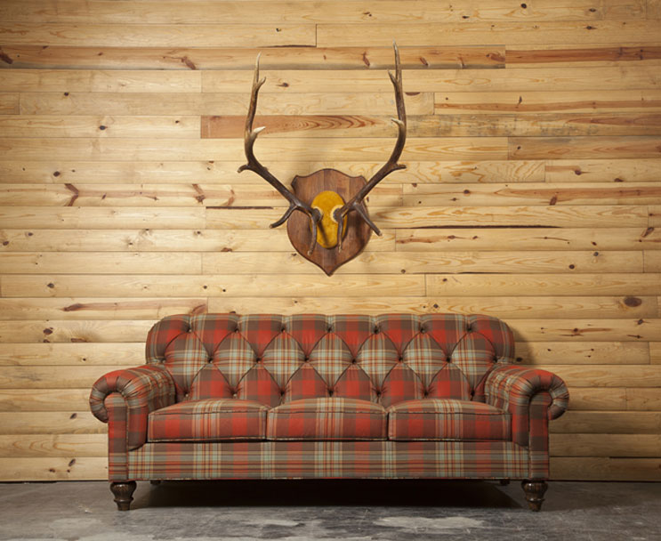 Plaid Tufted Sofa And Mounted Antlers