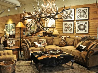large couch and antler chandelier, cowhide ottoman, feather art